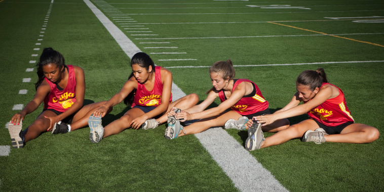 Teenage runners stretching before exercise
