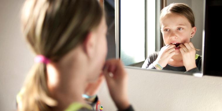 Girl flossing teeth in bathroom seen through mirror