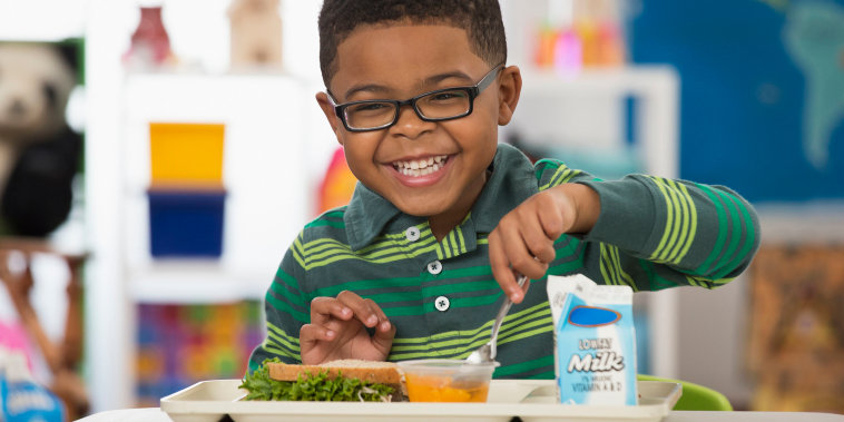Black boy eating lunch at school