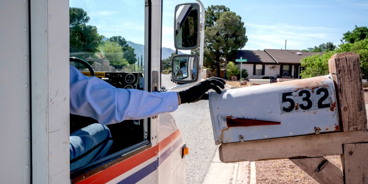 Image: A USPS mail carrier delivers mail in El Paso, Texas, on April 30, 2020.