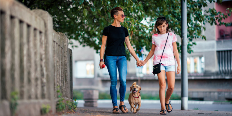 Mother and daughter walking on the street with a dog