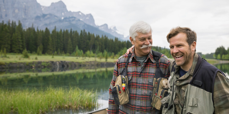 Father and son standing by still lake
