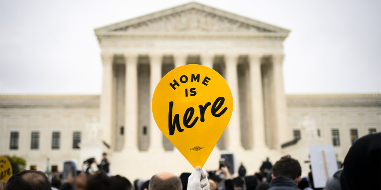 "A demonstrator holds a ""Home Is Here"" sign during a rally supporting the Deferred Action for Childhood Arrivals program (DACA) outside of the Supreme Court on Nov. 12, 2019."