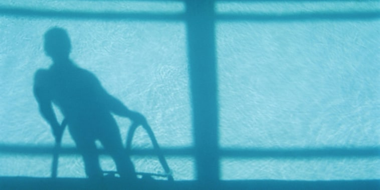 Man at poolside, low section, casting shadow on water, elevated view