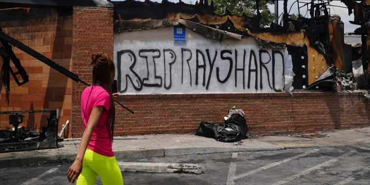 A woman uses her cell phone to document the damage to a burned Wendys restaurant following the police shooting death of Rayshard Brooks in the restaurant parking lot June 14, 2020, in Atlanta.