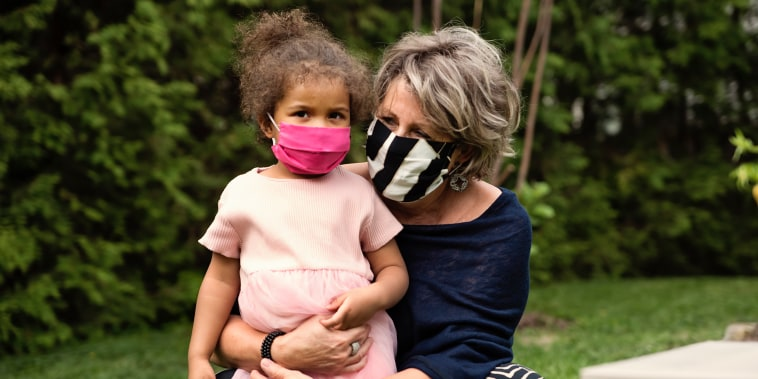 Grandmother holding toddler granddaughter with protective mask.