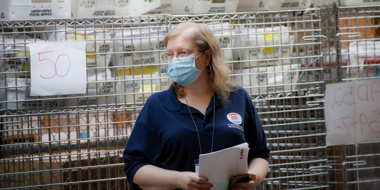 Cages loaded with ballots in United States Postal Service bins rest behind a worker at a Board of Elections facility in New York City on July, 22, 2020.