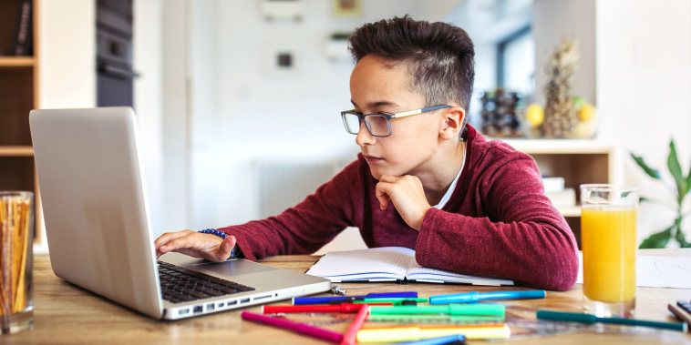 Boy doing homework on laptop surrounded by school supplies