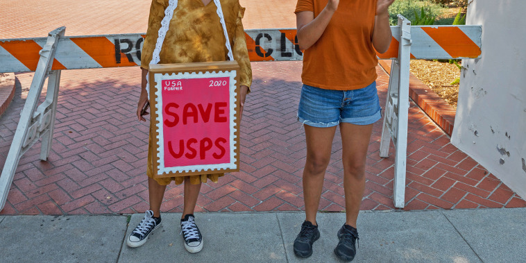 Protesters rally outside the home of USPS Board of Governors John M. Barger to decry recent cuts by Postmaster General Louis DeJoy that could affect presidential election mail-in ballots in San Marino, Calif., on Aug. 22, 2020