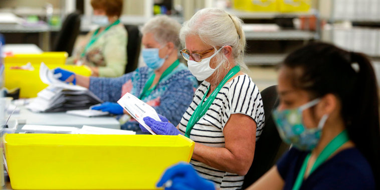 Image: Election workers wear masks and gloves as they open envelopes containing vote-by-mail ballots for the Aug. 4 Washington state primary