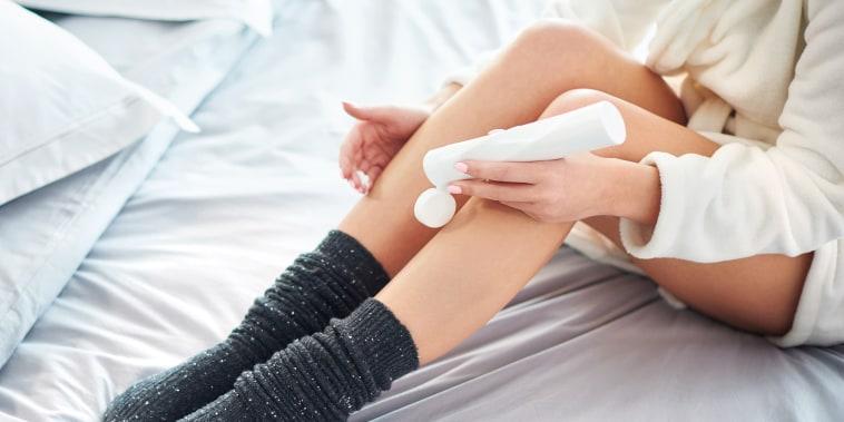 woman applying body lotion to legs