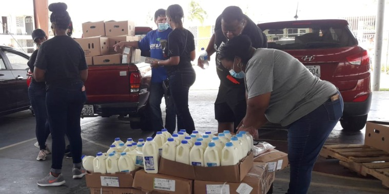 Volunteers help distribute milk in Loiza, Puerto Rico.