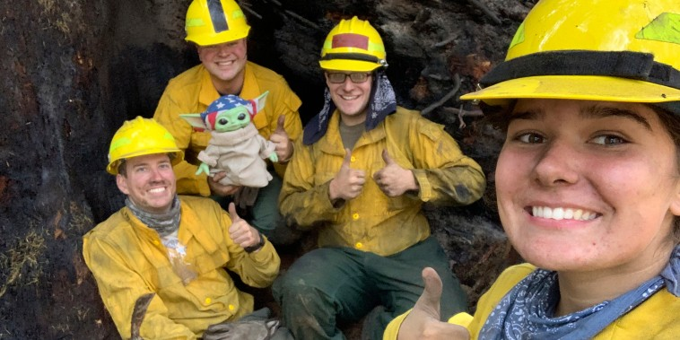 """Lucas Galloway, from left, Jaebyn Drake, Rhett Schieder and Audrey Wilcox pose for a selfie with Baby Yoda on Sept. 20, 2020, while fighting the Holiday Farm Fire in Blue River, Oregon. Beleaguered firefighters in the western United States have a new force on their side: Baby Yoda. In early September, A 5-year-old Oregon boy named Carver and his grandmother delivered a toy version of \""""The Mandalorian\"""" character to a donation center for firefighters. The toy came with a handwritten note from Carver saying the toy was meant to be \""""a friend\"""" in case they got lonely. Since then, Baby Yoda has been to four wildfires in two states. (Courtesy of Audrey Wilcox via AP)"""