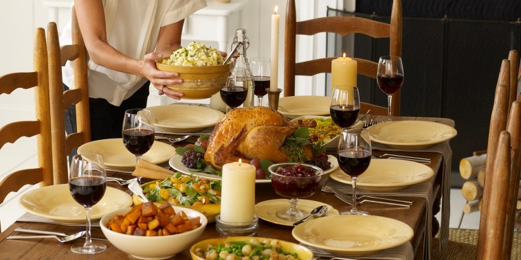 Woman setting table for Thanksgiving meal