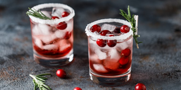Cranberry cocktail with ice. Christmas cranberry beverage in glasses decorated with sugar and rosemary