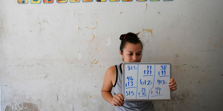 Image: Gabriela Fajardo, a 26-year-old Honduran seeking asylum in the United States, teaches a Zoom class for Central American children living in camps