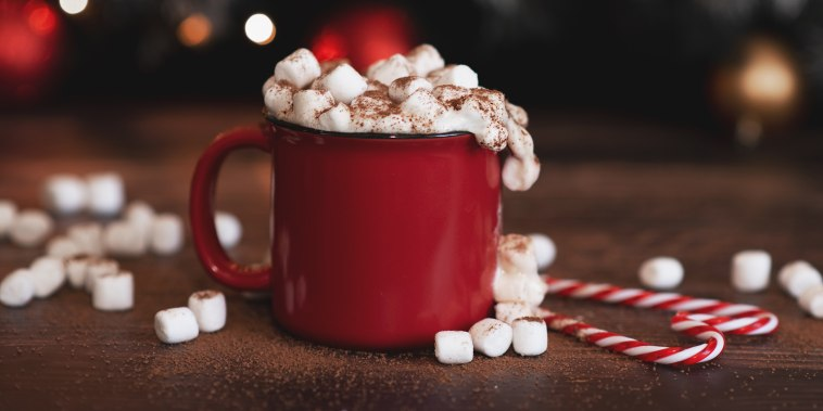 Winter whipped cream hot coffee in a red mug with star shaped cookies and warm scarf - rural still life