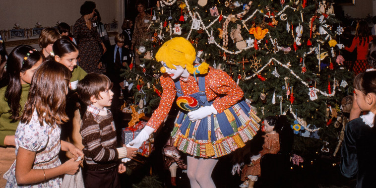 This photograph was taken by National Geographic photographer Joseph H. Bailey on December 16, 1975, during a Christmas party hosted by First Lady Betty Ford for the children of the Diplomatic Corps. Approximately 463 children from 84 countries were invited to the party, where they enjoyed entertainment by television puppetry personalities Kukla, Fran, and Ollie, clowns from the Social Security Clown Club from the Baltimore Social Security Administration, and an appearance by Santa Claus. The party was coordinated by THIS (The Hospitality and Information Service) for Diplomats, a volunteer organization established in 1961 to support newly appointed diplomats and their families transition to life in Washington, D.C. Here, children are greeted by clowns from the Social Security Clown Club as they admire the official White House Christmas tree in the Blue Room. During the 1970s, the Social Security Clown Club also entertained children at the White House Easter Egg Roll.