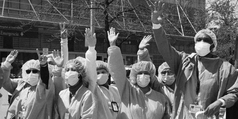 Healthcare workers at John H. Stroger Jr. Hospital clap and cheer as they watch the U.S. Navy's Blue Angels flight demonstration squadron fly over Chicago on May 12, 2020.