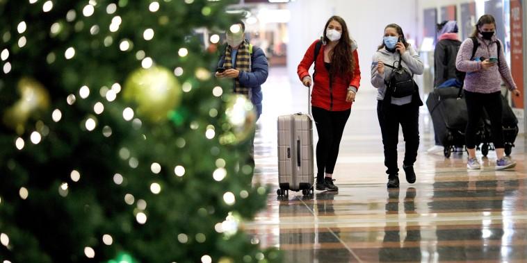 Holiday travelers wearing face masks are seen at Ronald Reagan Washington National Airport in Arlington, Va., on Dec. 23, 2020.