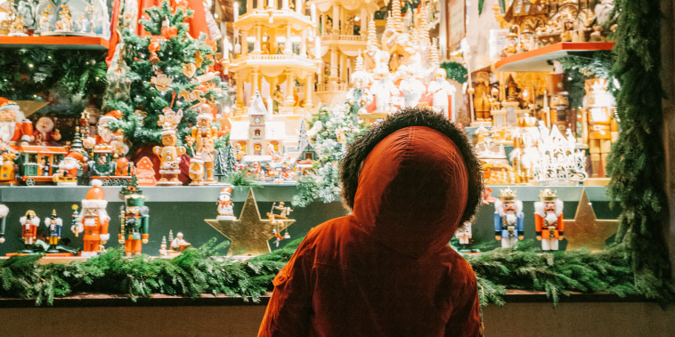Little boy looking at store window on Christmas