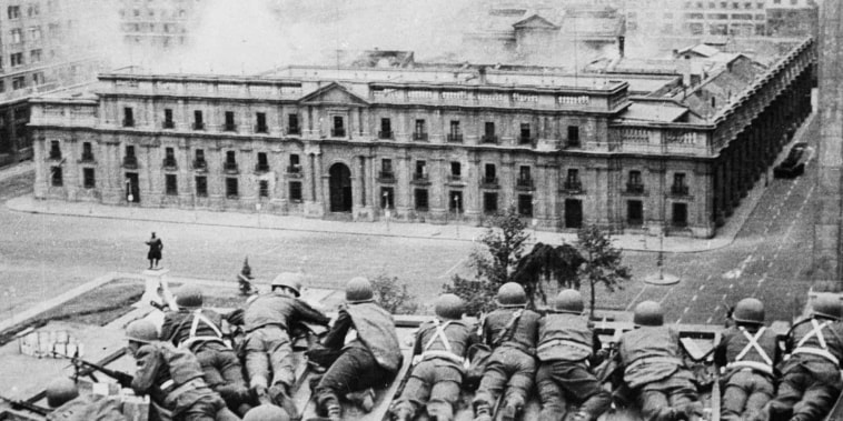 Soldiers supporting the coup led by Gen. Augusto Pinochet to overthrow Allende take cover as bombs are dropped on the Presidential Palace of La Moneda in Santiago, Chile, on Sept. 11, 1973.