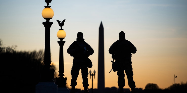 Image: National Guard soldiers are seen in silhouette as they keep guard in front of the Capitol Building and near the Washington Monument