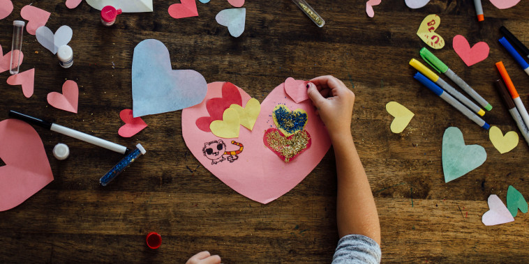 Overhead view of girl creating valentines crafts and cards