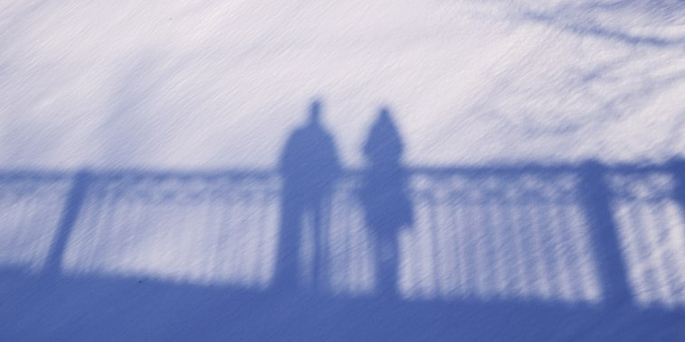 Shadow silhouette of couple man and woman standing on a bridge on snow background on sunny winter day