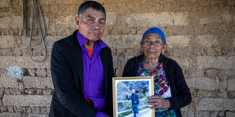 Image: German and Maria Tomas pose for a photograph holding a framed portrait of their grandson Ivan Gudiel, at their home in Comitancillo, Guatemala