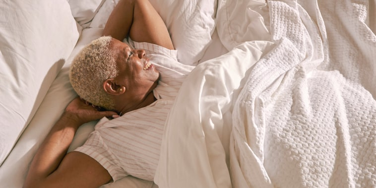 Woman relaxing in bed with her new sheets and mattress she gifted herself
