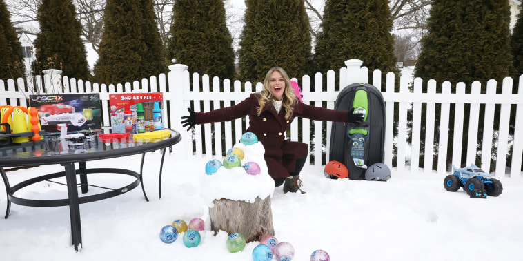 Woman showing toys on snow