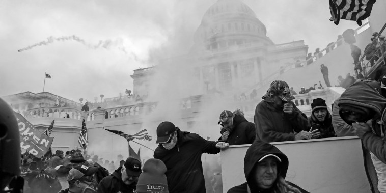 Supporters of President Donald Trump cover their faces to protect from tear gas during a clash with police in front of the Capitol on Jan. 6, 2021.