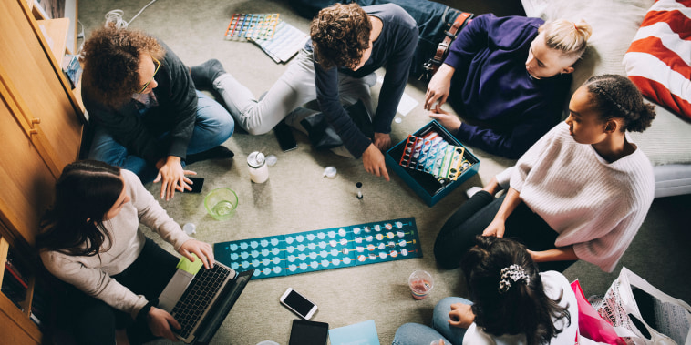 High angle view of teenage girls and boys playing board game in bedroom
