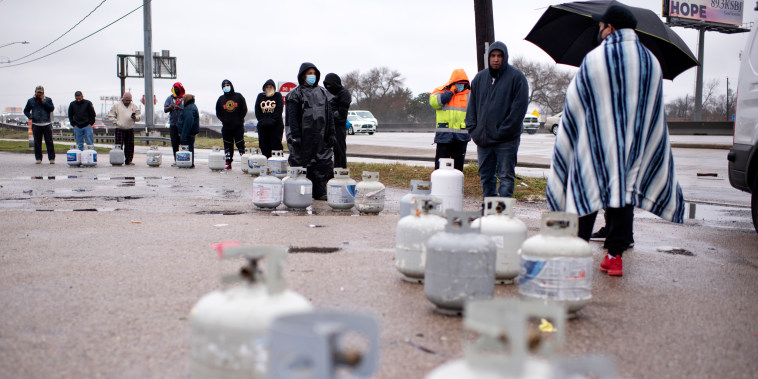 Propane tanks are placed in a line as people wait for the power to turn on to fill their tanks in Houston on Feb. 17, 2021.
