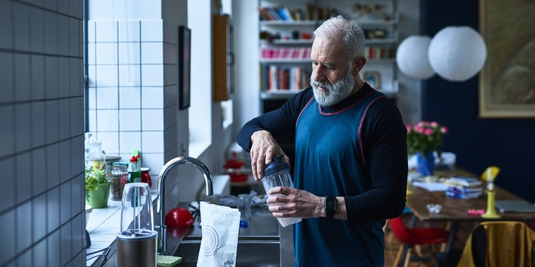 Senior man making protein shake before exercising