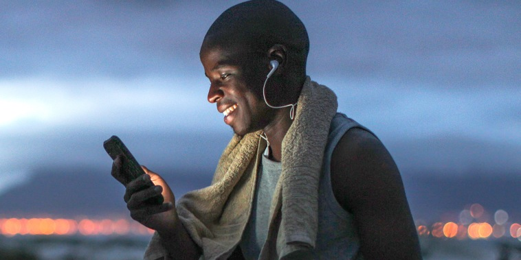 a Young black man in exercise clothing outdoors before sunrise