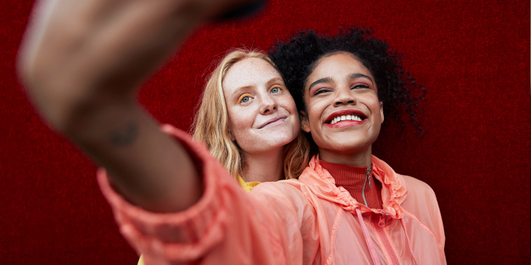 Close-up of smiling young women taking selfie while standing against red wall