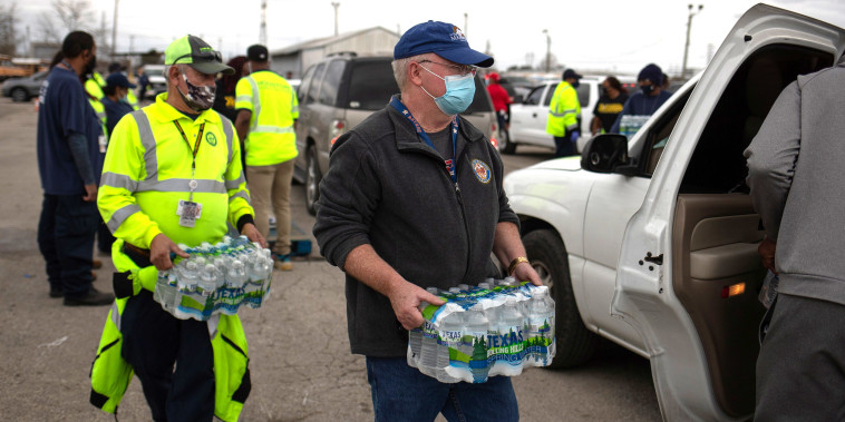 Image: Volunteers deliver water to local residents in vehicles at Butler Stadium after an unprecedented winter storm in Houston
