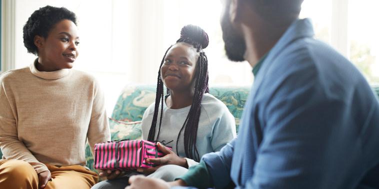 Teenage girl holding gift sitting on sofa at home