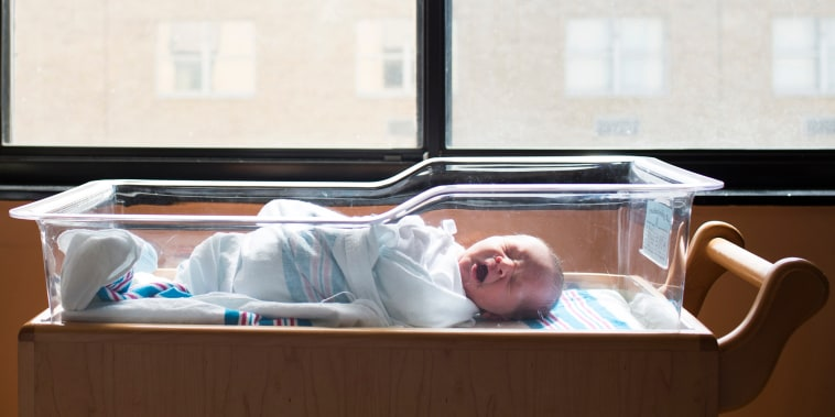 Baby boy yawning while sleeping in crib by window at hospital