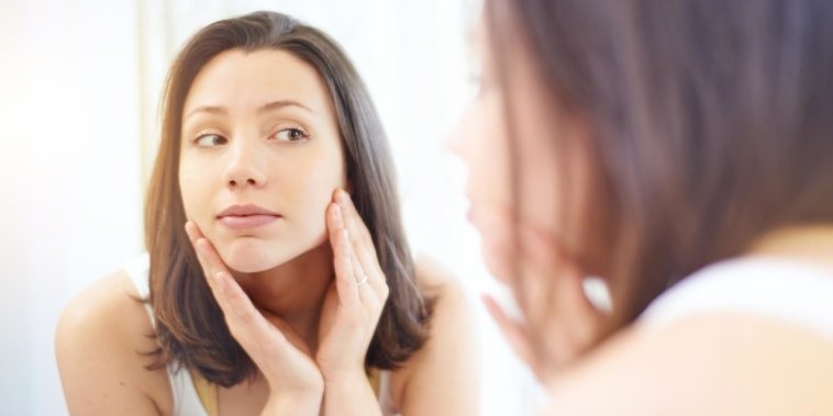Woman touching her face and looking in the mirror after getting dermaplaning