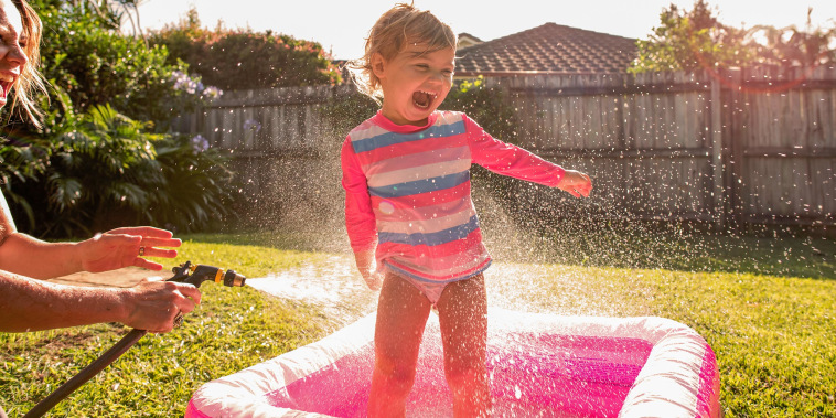 Little girl playing in a pink kiddy pool in the backyard, while her mom sprays her with the house