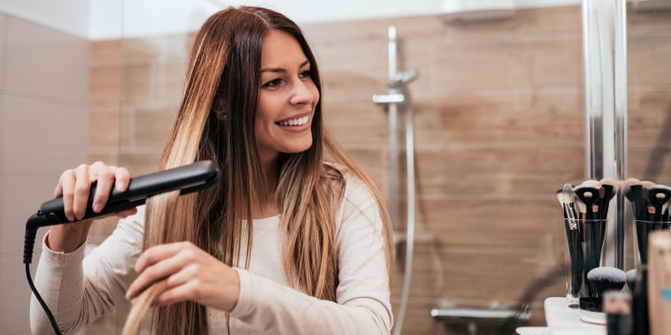 Woman straightening her hair in the bathroom with her hair iron