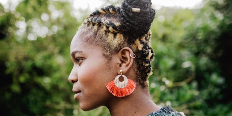 Side profile of a Woman outside, wearing a beautiful orange earring