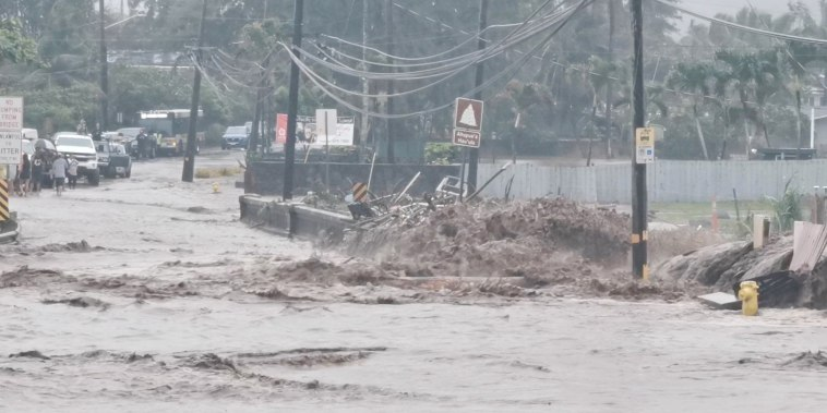 Floodwaters stream down a street in Hauula, Hawaii, on March 9, 2021.