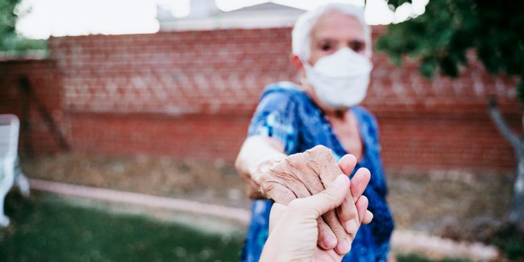 Older woman in backyard wearing an Kn95 mask and holding someones hand. The CDC updated their guidelines on how to shop for face masks and how vaccinated people can socialize. Learn about the updates for face masks and more.