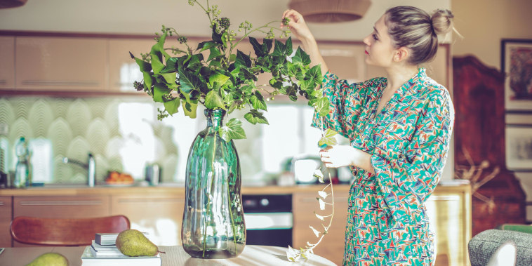 Woman standing in her kitchen touching her flowers, wearing a colorful floral green silk robe