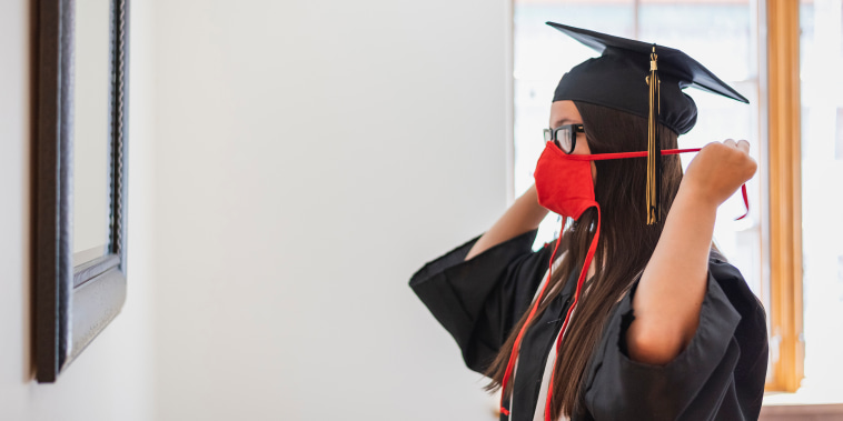 Teenage girl in cap and gown putting on face mask