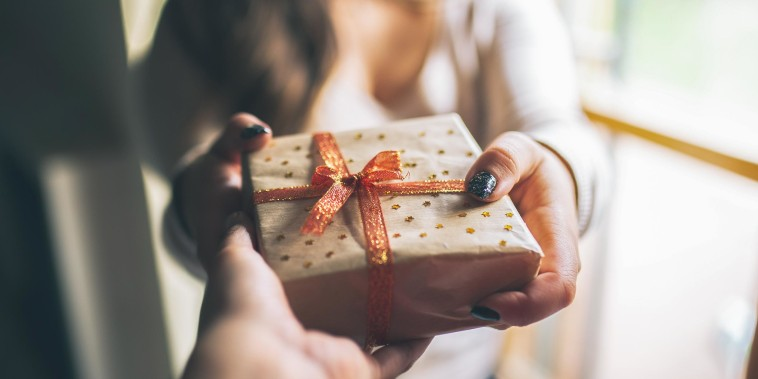 Someone giving a wrapped gift